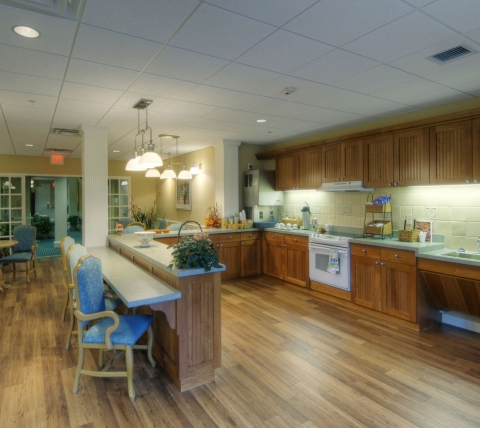 Large kitchen with bar seating and light brown cabinetry.