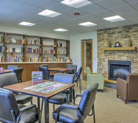 Library with tables, fireplace and bookshelves at Luther Village III