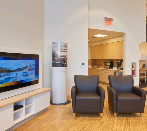 customer waiting area at car dealership with chairs and television