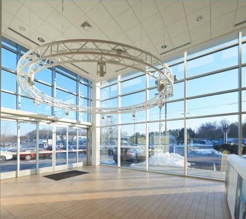 steel circle hanging in car showroom with huge windows behind it