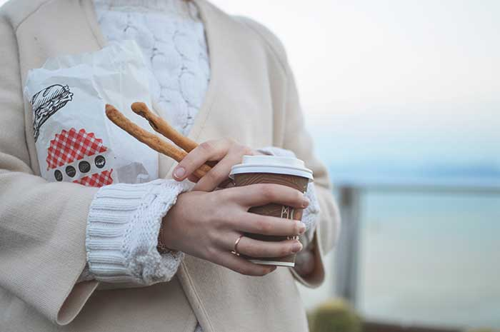 woman tan blazer holding coffee bread sticks